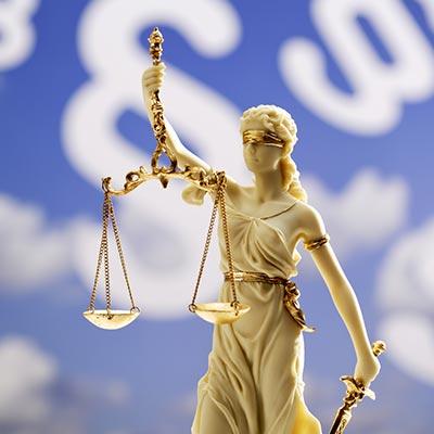 Złota statuetka adwokata zaopatrzonego w wagę spotykana jako ozdoba w kancelariach prawnych