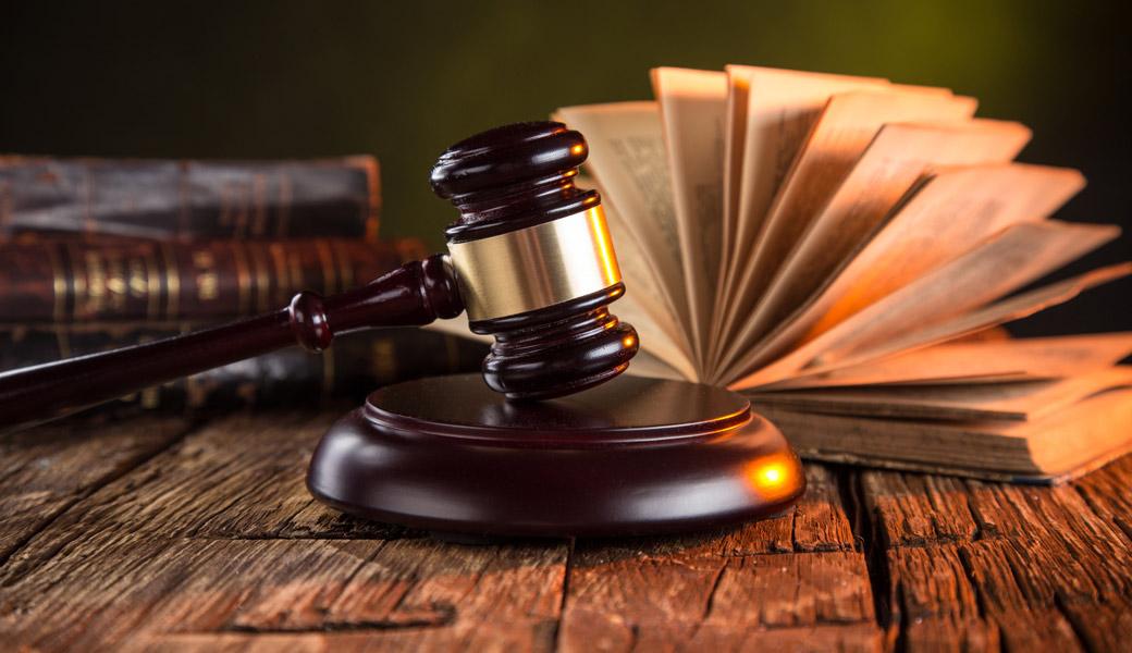 Książka i młotek sędziego podczas rozpraw sądowych prowadzonych przez usługi prawnicze